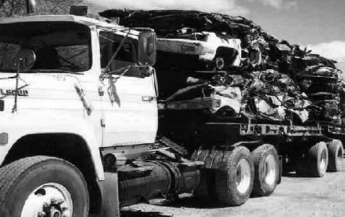Black and White photo of a truck carrying crushed cars