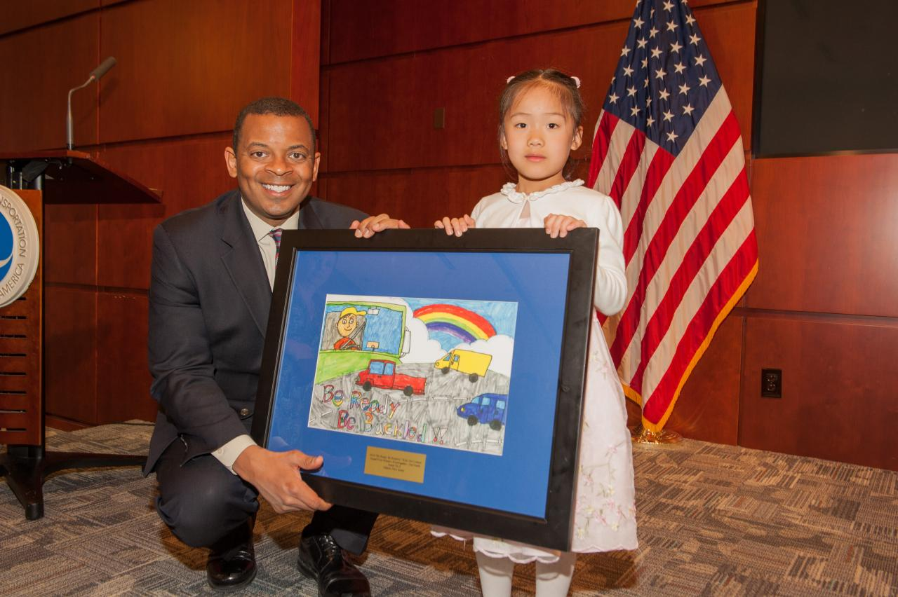 "DOT Secretary Anthony Foxx with first-grader Annie Yu from Edison, N.J., who won top honors in the grades K-2 category for the 2014 ""Be Ready. Be Buckled."" student art contest."