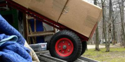 A large cart carrying supplies vertically sliding out of a truck