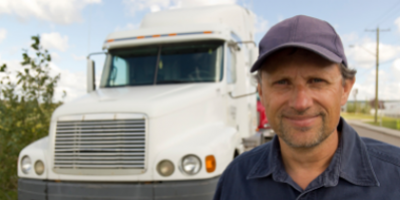 Image of a driver smiling in front of a truck