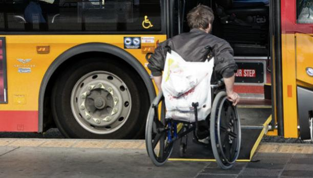 man in wheelchair boarding bus