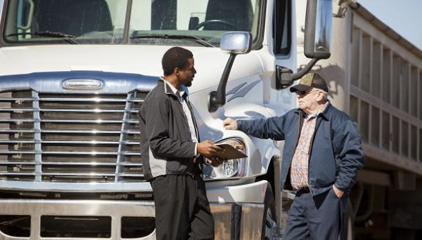 Individual talking in front of a large truck