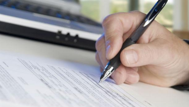 Hand with pen on top of application form